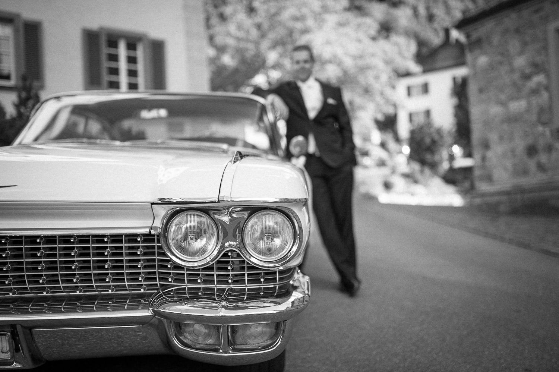 Hochzeitsfoto vom Bräutigam am Oldtimer in Vaduz, Liechtenstein auf dem Weg nach Schaan.