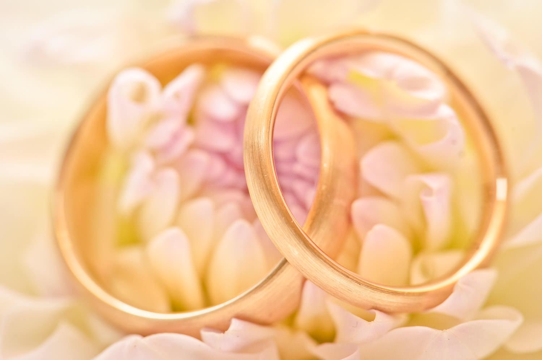 Goldene Eheringe auf Blumenschmuck fotografiert bei einer Hochzeit in Dornbirn.