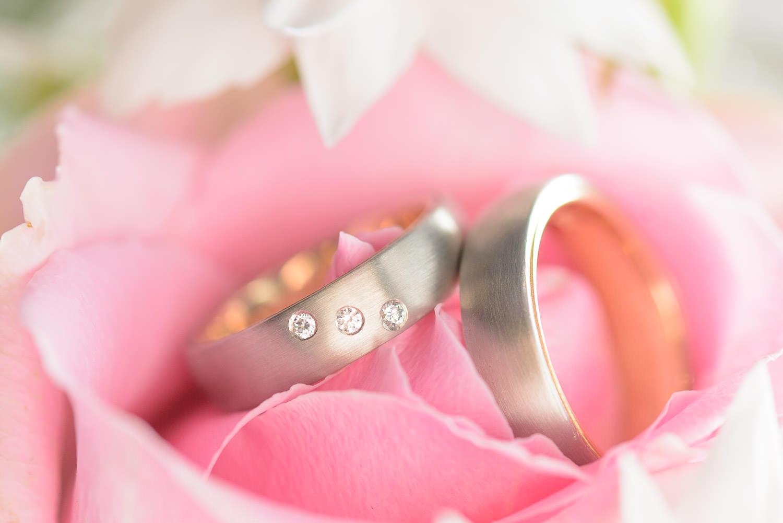 Eheringe, Hochzeitsringe oder Trauringe schön fotografiert mit Makro und Blitz, Gold, Weißgold und Diamanten auf einer Rose.